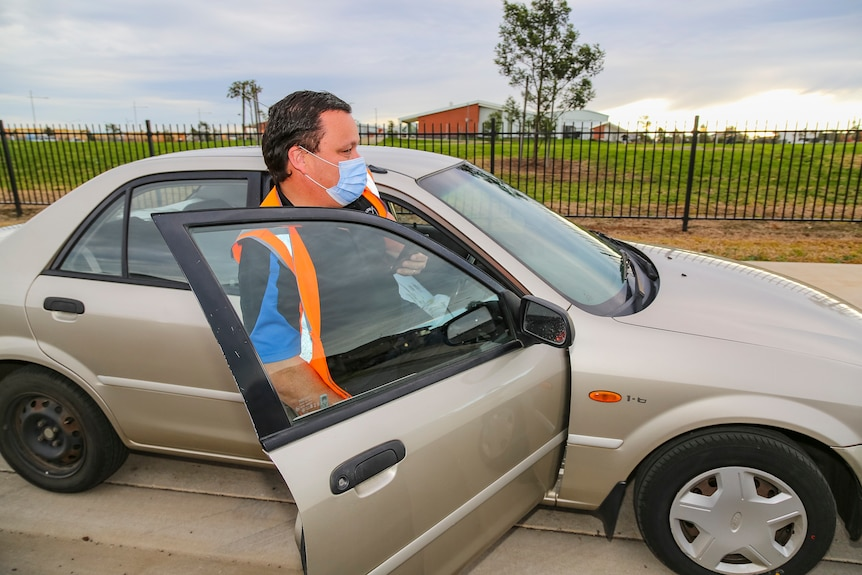 A man in an orange high-vis vest and surgical face mask gets back into his car.
