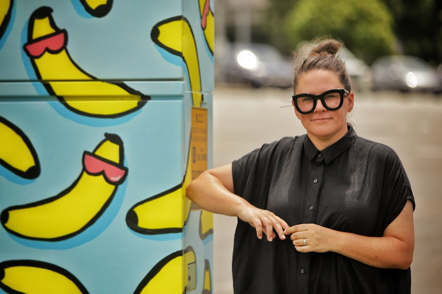 Street artist Tamara Scheiwe stands beside a traffic signal box with painted bananas on it.