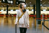 A woman wearing a face mask rests a hand on her suitcase at an airport