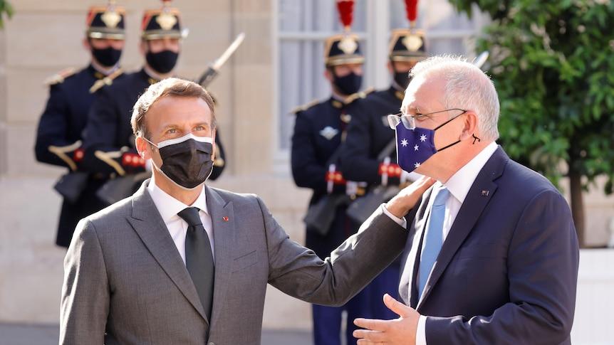 French President Emmanuel Macron puts his hand on the shoulder ofAustralian Prime Minister Scott Morrison