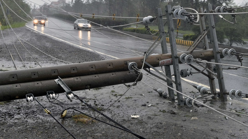 Cars drive past collapsed power lines, as super typhoon Meranti skirts Pingtung county in southern Taiwan.