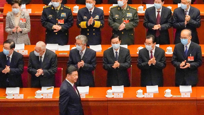 Xi Jinping saunters past a row of applauding Chinese delegates in masks