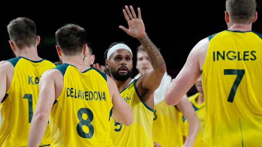 Australia basketball captain Patty Mills raises his hand as teammates walk around him.