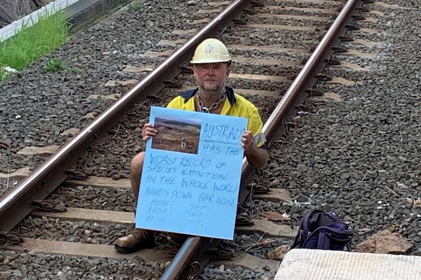 A protester wearing a hard hat and high vis holding a sign about species extinction sits on train tracks at Bowen Hills.