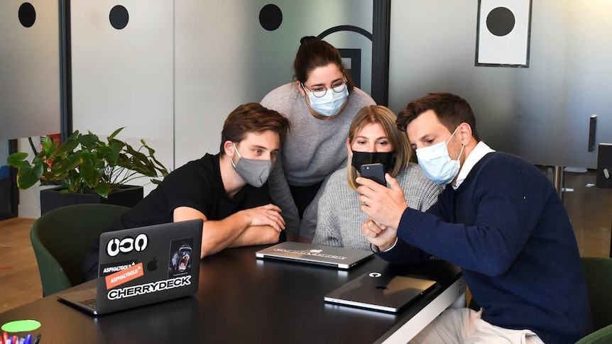 Four workers sit around a table wearing face masks and looking at a phone, in a story about managing back-to-work anxiety.