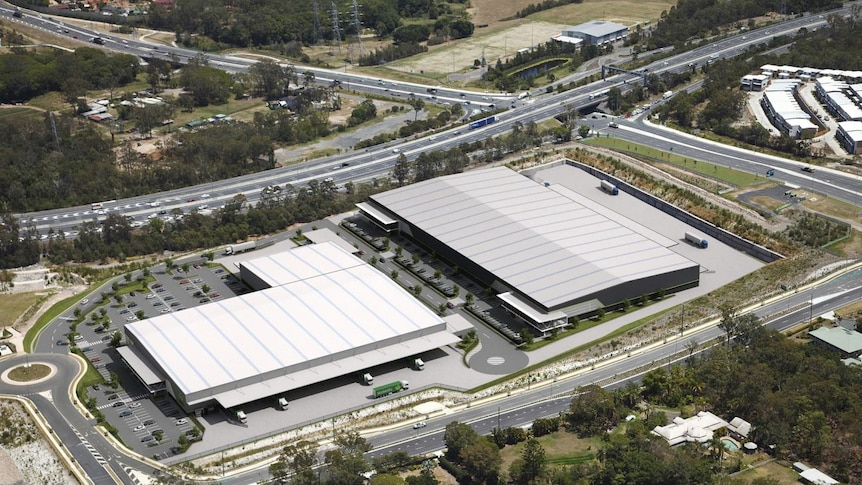 An aerial shot of two large warehouses alongside main roads.
