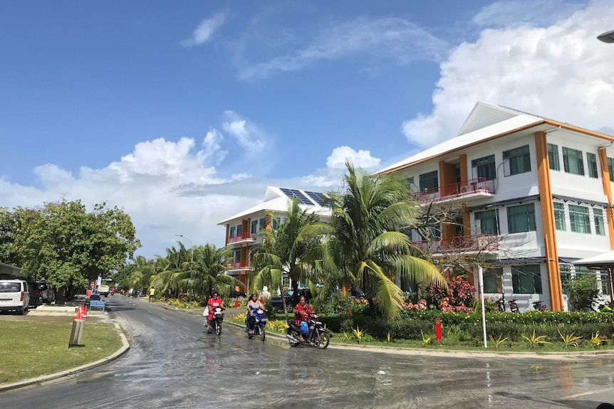 People ride motorcycles down a tree lined suburban street.