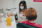 a masked pharmacist preparing a vaccine shot with a woman