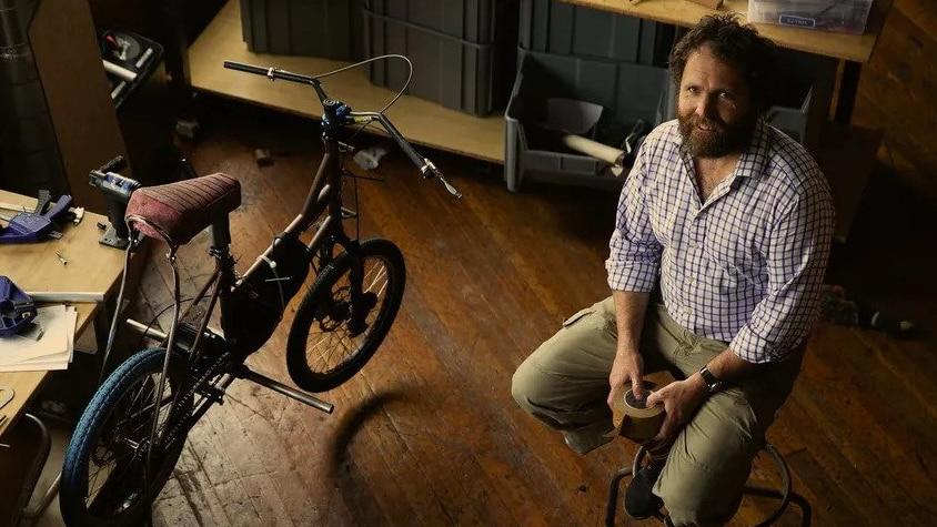 A bearded middle-aged man sits on a stool beside a bike