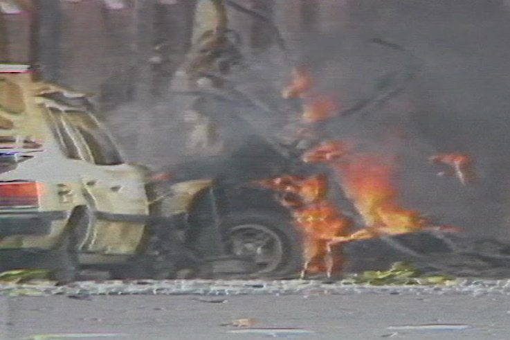 A grainy image of a wrecked car on fire.