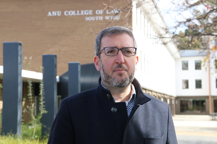 A man stares part the camera with a serious expression at the front of a university building.