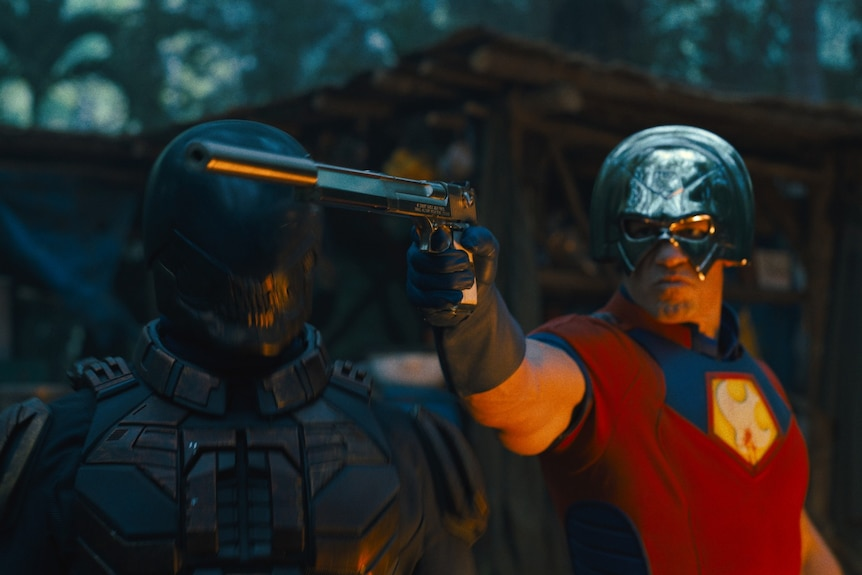 A man in a red superhero outfit, including a metal helmet, holds out a gun. Next him is another man in a black full body suit.