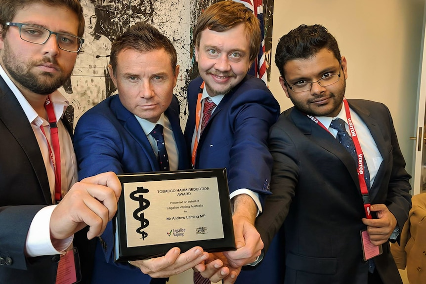 Andrew Laming MP poses with an award from three vaping activists.
