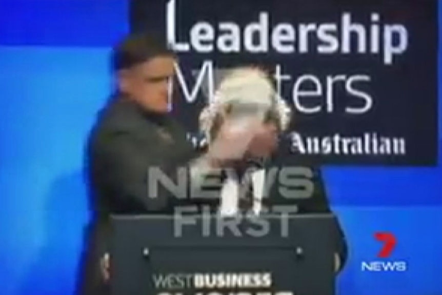 A man hits Qantas CEO Alan Joyce in the face with a cream pie after walking up behind him on stage.