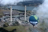 """A hot air balloon featuring the words """"Save the climate — No future in coal"""" flies over a power station."""