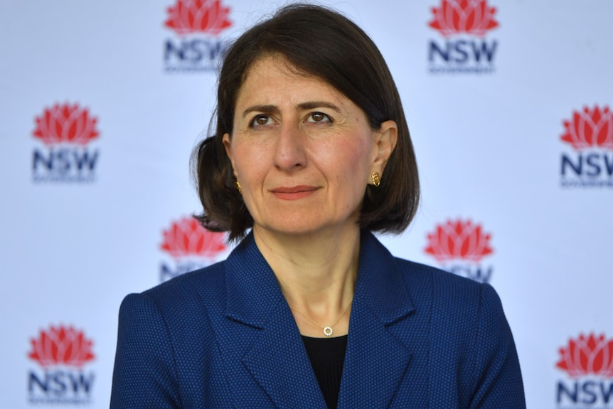 NSW Premier Gladys Berejiklian wearing blue in front of a NSW Government sign at a coronavirus media conference.