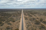 A road stretches off into the horizon, not a vehicle in sight