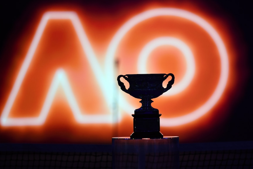 The Australian Open mens final trophy on display ahead in front of an illuminated AO.