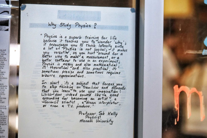 A written 'Why study physics' quote on a piece of white paper stuck on a glass wall in a classroom.