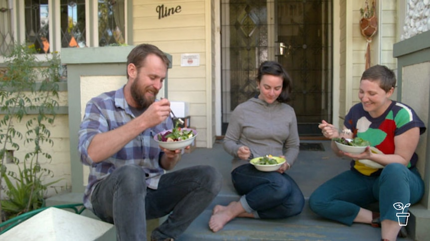 Man and two women sitting on front steps of house eating bowls of salad