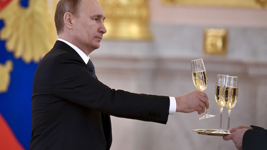Vladimir Putin taking a glass of champagne from a waiter.