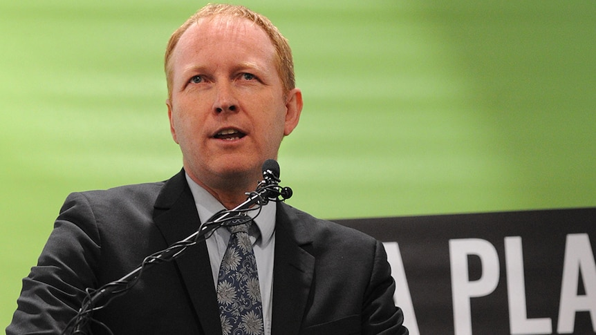 Man in suit giving a speech in front of a Greens banner.