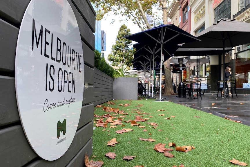 A sign saying Melbourne is open, come and explore, next to artificial lawn and a cafe.