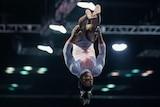 Simone Biles vaults with her legs straight