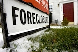 A foreclosure sign sits in front of a townhouse