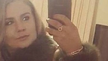 A woman raises her smartphone to take a selfie in the mirror