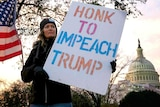 """Christina Young holds a """"Honk to Impeach Trump"""" sign outside of Longworth House Office Building"""