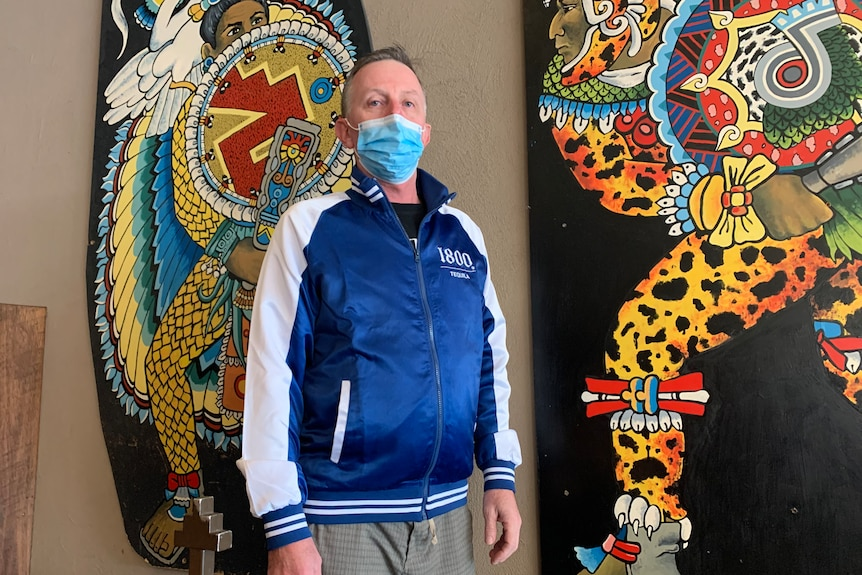 a man stands with a mask on outside a mexican restaurant