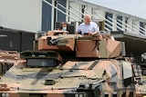 The Prime Minister smiles as he sits atop a tank driving down a street.
