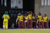 An Australian batsman trudges off as the West Indies cricketers celebrate victory on the oval.