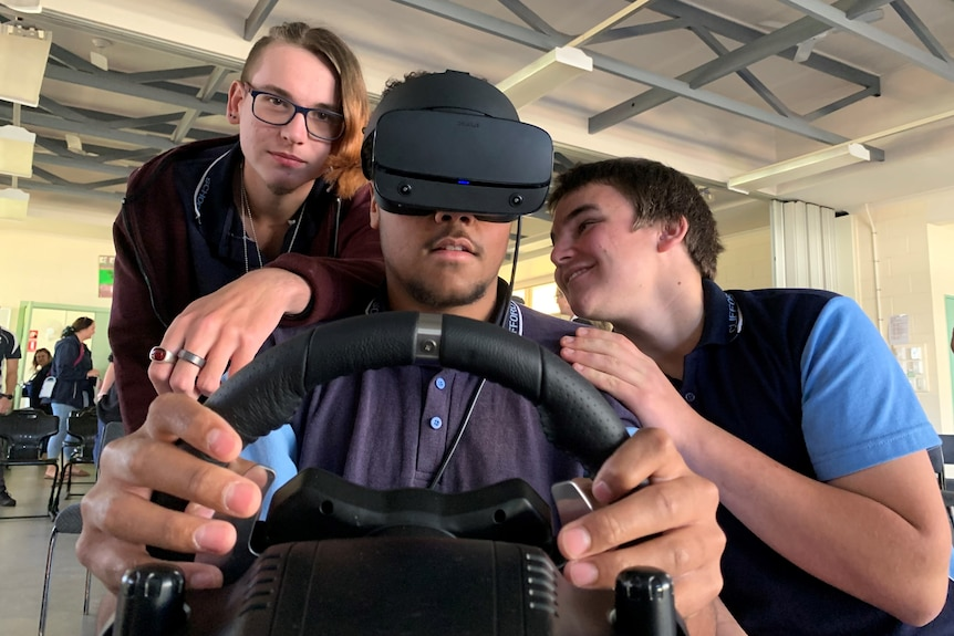 A teenage boy using a VR headset and steering wheel while two friends give him advice.