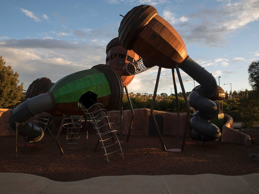 An empty playground in Canberra lit by the golden evening sunlight