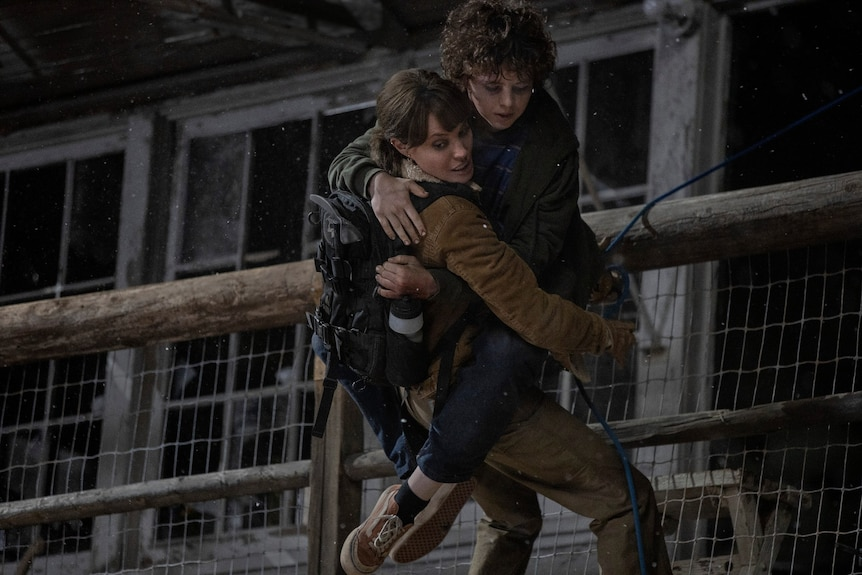 Film still of Angelina Jolie as Hannah holding Finn Little as Connor climbing down a wall from Those Who Wish Me Dead