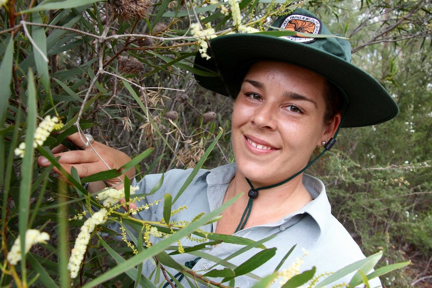 A young woman, Jacinta Rheinberger, wearing a Discovery ranger uniform and hat, inspects a wildflower.