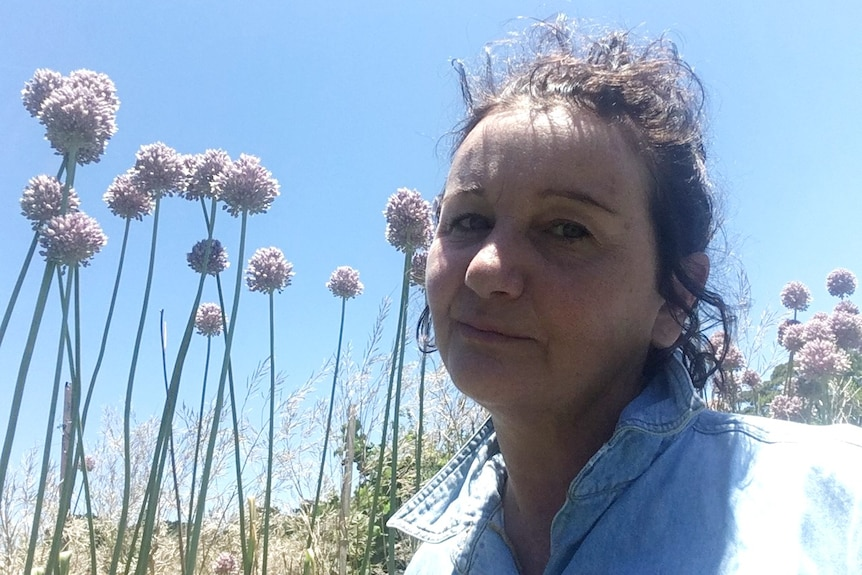 Close up photo of a white woman with black curly hair with garlic flowers and blue sky behind her