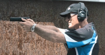 Steve Dickson, wearing a hat, sunglasses and ear protectors, poses with a gun in a firing range.