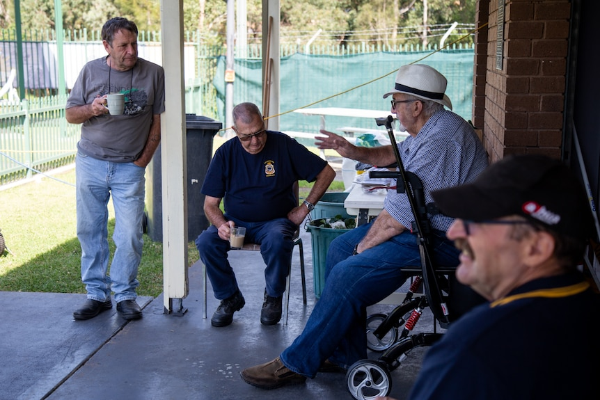 a man standing up leaning against a pole and holding a mug with three men sitting on chairs under a pergola