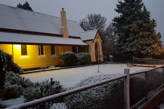 A building with a dusting of snow on it.