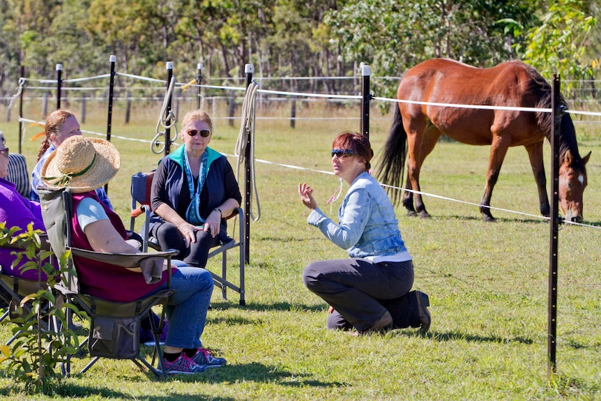 Helena Botros kneels as she speaks to four women in the horse paddock, she has red hair and wears sunglasses. Mid 30s.