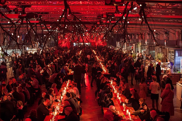 A large group of people gather in a dark dining hall under red lighting.