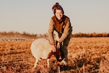 Female farm worker stands in a paddock smiling at camera whilst assessing a sheep