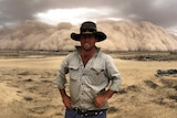 A farmer stands on a dusty property with his hands on his hips as a large dust storm rolls in and looms behind him.