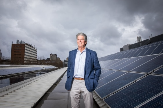 A man with grey hair and wearing a blue suit jacket on a rooftop with solar panels