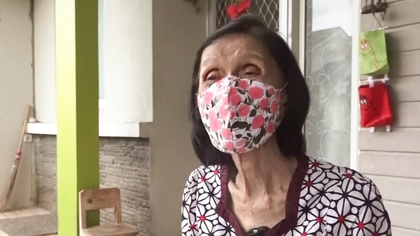A woman with dark hair and wearing a floral mask and patterned shirt looks at the camera.