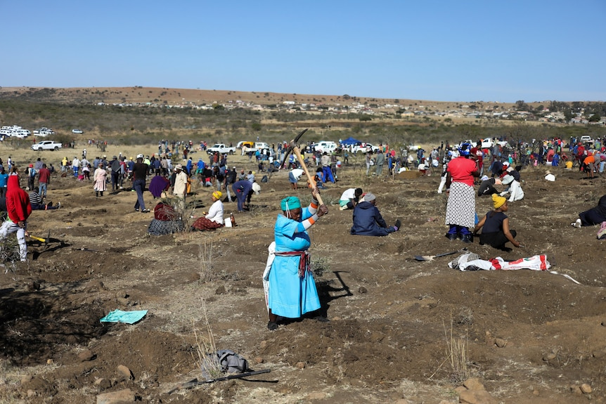 The hillside where villagers flocked to dig for diamond with a woman in foreground using a pickaxe to dig