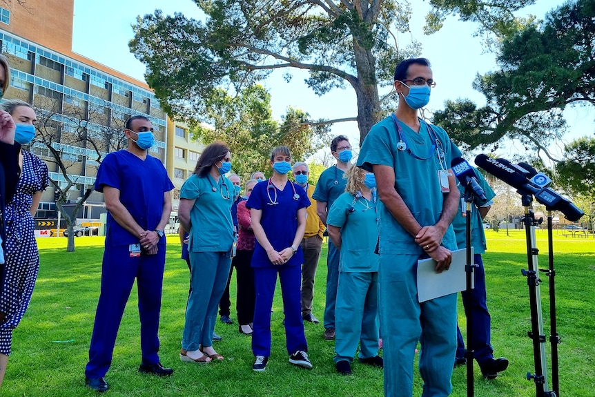 Doctors and nurses in their blue and green scrubs stand in front of media microphones in the Adelaide parklands
